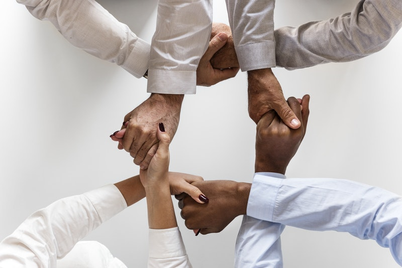 A group of office working holding hands to symbolize collaboration on high-quality, often short eLearning videos.